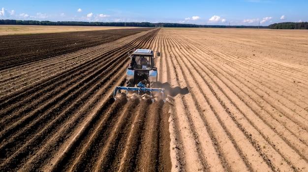 Trattore - vista aerea di un trattore sul lavoro - coltivare un campo in primavera con cielo blu - macchine agricole Foto Premium