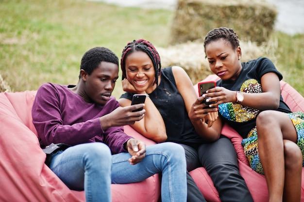 Tre amici afroamericani si rilassano, sedendosi sui pouf e usando i loro telefoni all'aperto. Foto Premium