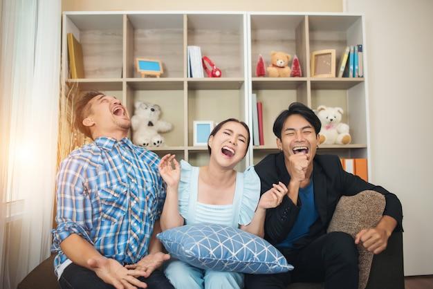 Tre amici felici che parlano e grande che ride dopo la visualizzazione della storia di scherzo Foto Gratuite