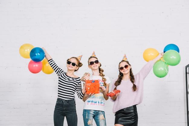 Tre amici femminili adolescenti che tengono i contenitori di regalo avvolti che stanno contro il muro Foto Gratuite