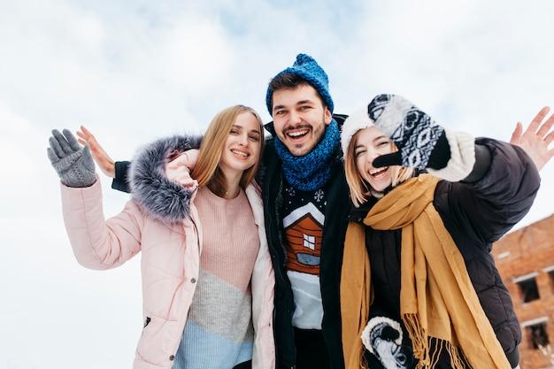Tre amici in abiti invernali agitando con le mani fuori Foto Gratuite