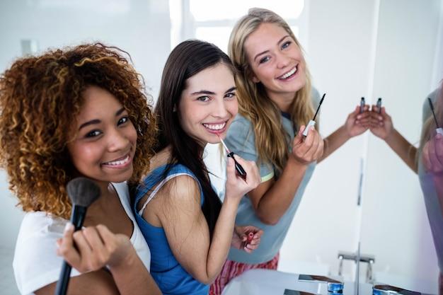 Tre amici sorridenti che mettono insieme il trucco nel bagno Foto Premium