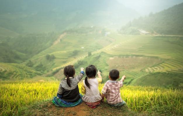 Tre bambini seduti fianco a fianco, vista posteriore per indicare le risaie. Foto Premium