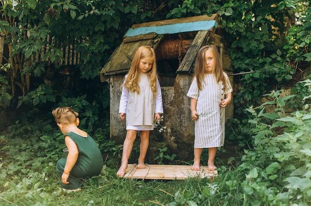 Tre bambini stanno giocando vicino al pozzo su uno sfondo di erba e alberi Foto Premium