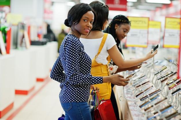 Tre bei clienti afroamericani ben vestiti delle ragazze con i sacchetti della spesa colorati nel negozio del telefono cellulare che sceglie smartphone. Foto Premium