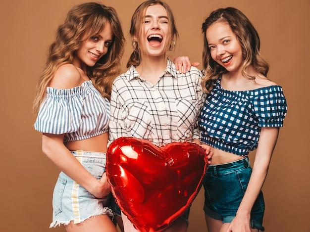 Tre belle donne sorridenti in abiti a scacchi estate camicia. ragazze in posa modelli con palloncino a forma di cuore rosso in occhiali da sole. pronto per la festa di san valentino Foto Gratuite