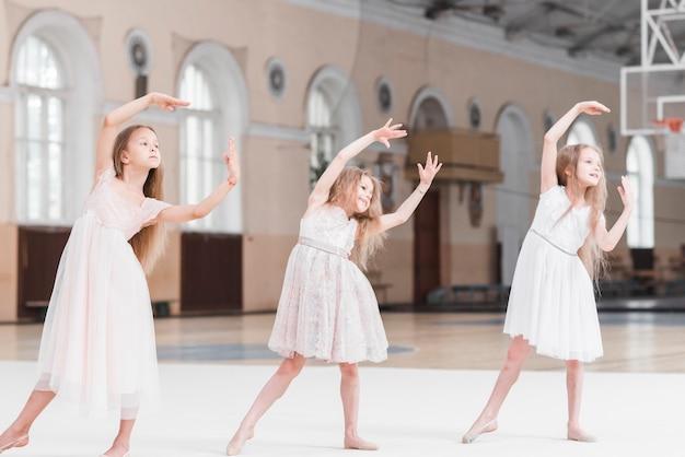 Tre belle ragazze della ballerina che ballano nella classe di ballo Foto Gratuite