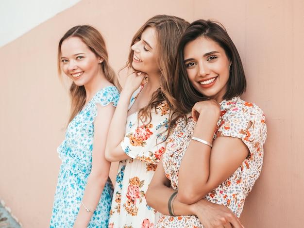 Tre belle ragazze sorridenti in prendisole alla moda estate in posa sulla strada Foto Gratuite