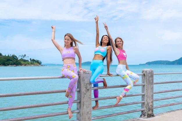 Tre bellezze sono in piedi sul molo e in posa in abiti moderni per il fitness. Foto Premium