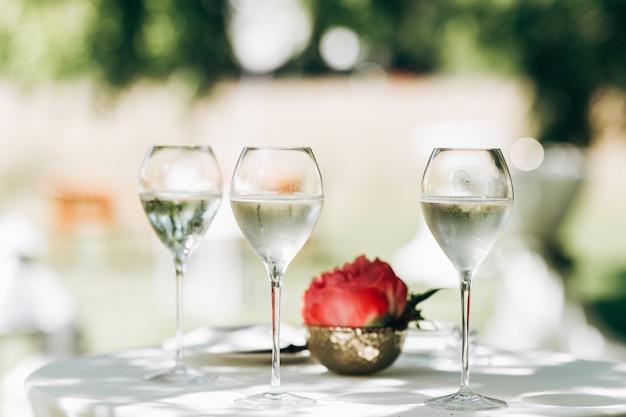 Tre bicchieri con acqua e peonia rossa stanno sul tavolo Foto Gratuite