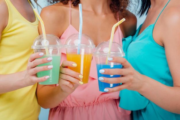 Tre bicchieri di plastica con diversi colori di succo in tre mani Foto Premium