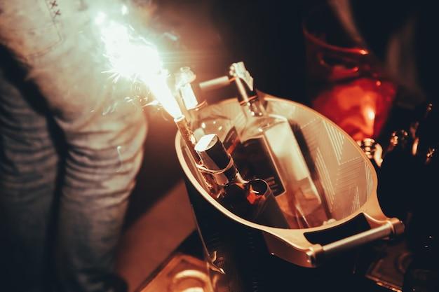 Tre bottiglie di alcool con i chiarori alla tavola della discoteca di notte nella città di barcellona. Foto Premium