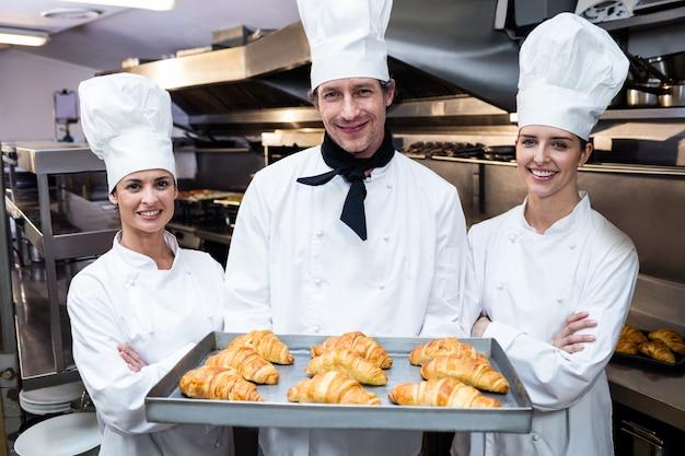 Tre chef in possesso di un vassoio di cornetto al forno Foto Premium