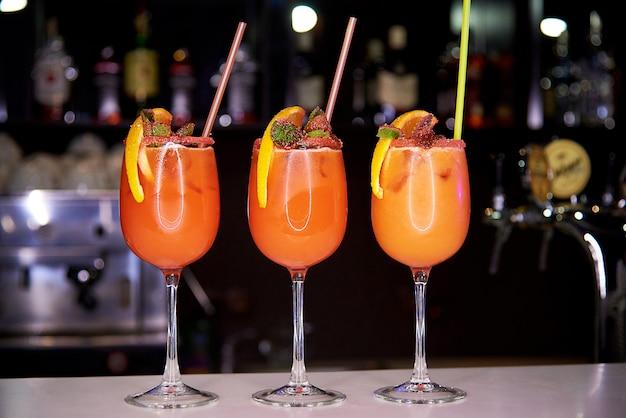 Tre cocktail freddi arancioni decorati con briciole di zucchero Foto Premium