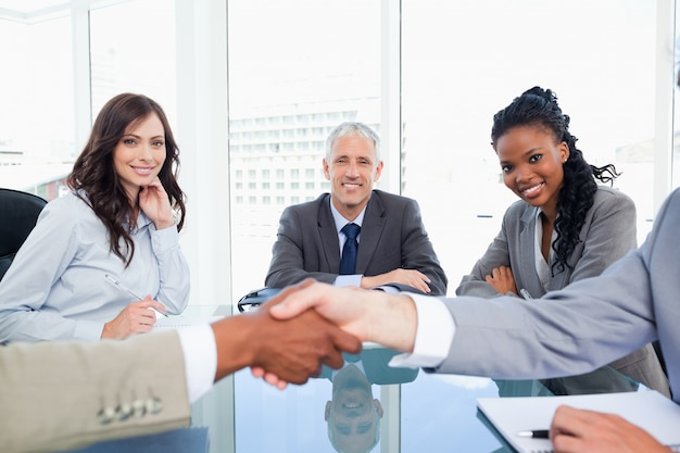 Tre colleghe sorridenti che esaminano due genti di affari che agitano le mani Foto Premium