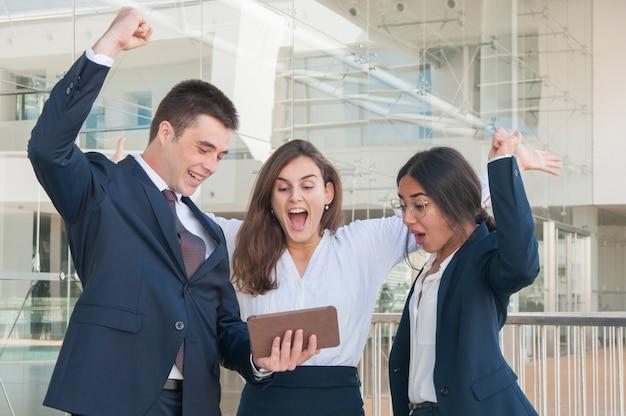 Tre colleghi esultano, ricevono buone notizie, alzando le mani Foto Gratuite