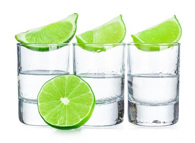 Tre colpi di tequila con calce isolata su bianco Foto Premium