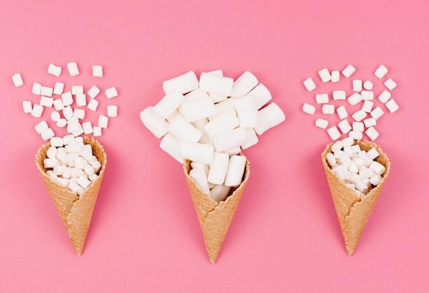 Tre coni waffle con marshmallow sul tavolo Foto Gratuite