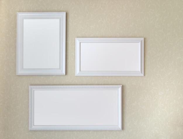 Tre cornici in legno bianco appeso a parete morbida gialla mock up modello Foto Premium