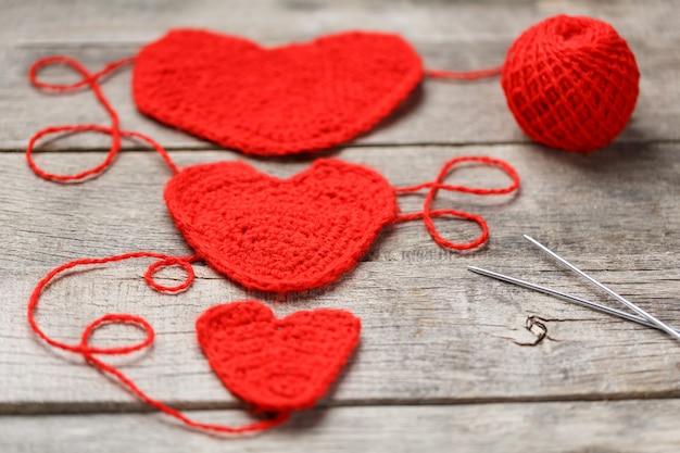 Tre cuori a maglia rossi, che simboleggiano l'amore e la famiglia. relazione familiare, legami. Foto Premium