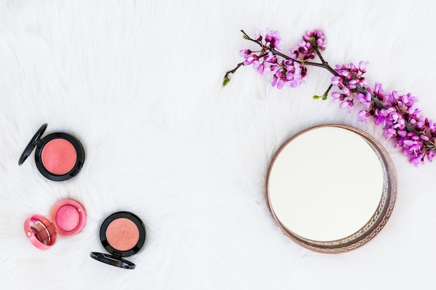 Tre diversi tipi di polvere compatta rosa con specchio e fiore ramoscello su sfondo di pelliccia bianca Foto Gratuite