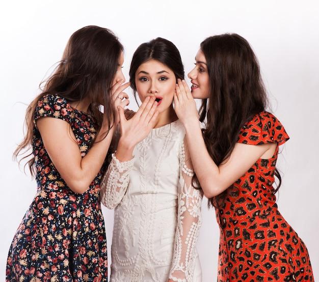 Tre donne sorridenti che bisbigliano gossip Foto Premium