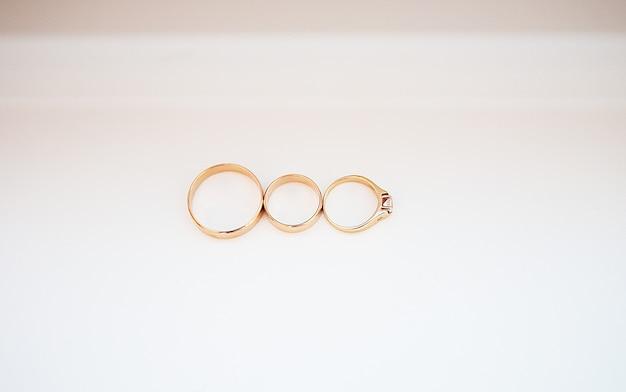 Tre fedi nuziali su fondo bianco Foto Premium