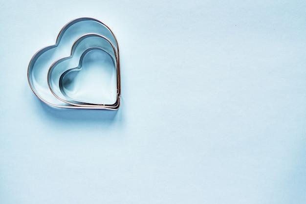 Tre formine per biscotti in metallo a forma di cuore su sfondo azzurro con spazio di copia Foto Premium