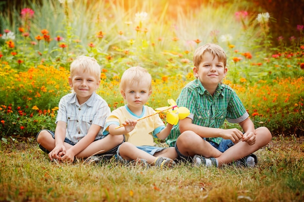 Tre fratelli piccoli che si siedono sull'erba nel giorno di estate soleggiato. Foto Premium