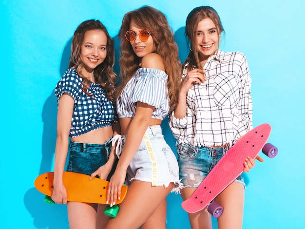 Tre giovani belle ragazze sorridenti alla moda con i pattini variopinti del penny. donna nella posa a quadretti dei vestiti della camicia di estate. modelli positivi che si divertono Foto Gratuite