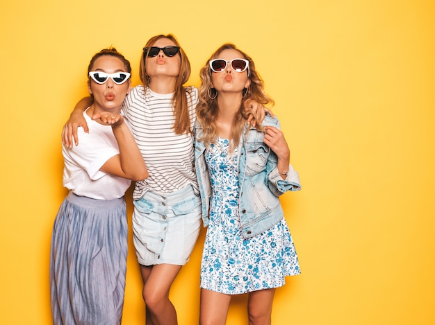 Tre giovani belle ragazze sorridenti hipster in abiti estivi alla moda. donne spensierate sexy che posano vicino alla parete gialla. modelli positivi che si divertono. in occhiali da sole. tre giovani bellezze Foto Gratuite