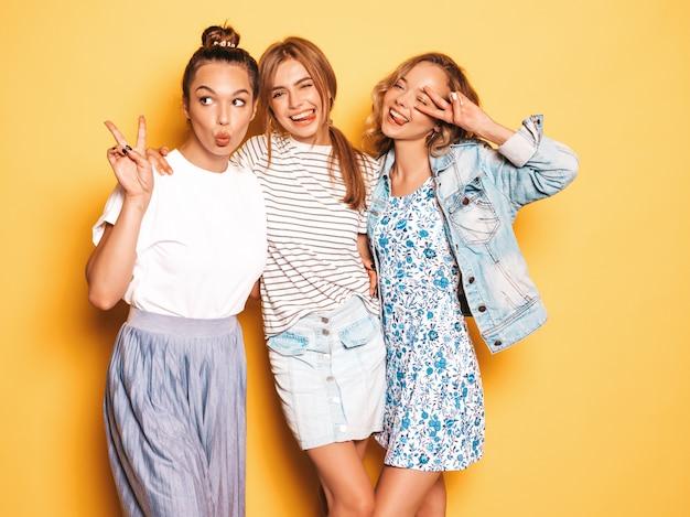 Tre giovani belle ragazze sorridenti hipster in abiti estivi alla moda. donne spensierate sexy che posano vicino alla parete gialla. modelli positivi che si divertono Foto Gratuite