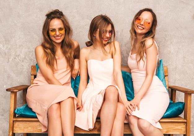 Tre giovani belle ragazze sorridenti in abiti alla moda estate rosa. donne spensierate sexy che si siedono sul sofà nell'interno di lusso. modelli positivi in occhiali da sole rotondi che si divertono e comunicano Foto Gratuite