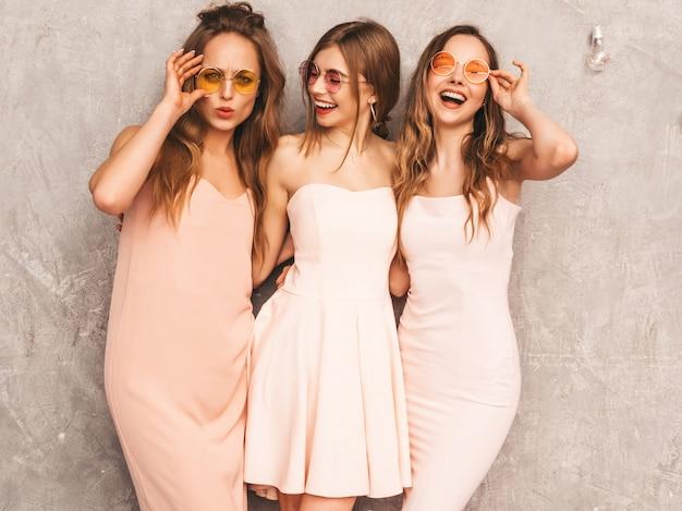 Tre giovani belle ragazze sorridenti in abiti rosa chiaro alla moda estate. posa sexy spensierata delle donne. modelli positivi in occhiali da sole rotondi che si divertono Foto Gratuite