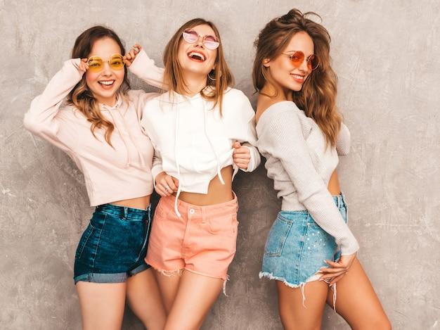 Tre giovani belle ragazze sorridenti in abiti sportivi alla moda estate. posa sexy spensierata delle donne. modelli positivi in occhiali da sole rotondi che si divertono. abbracciare Foto Gratuite