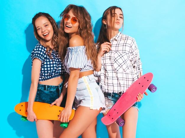 Tre giovani belle ragazze sorridenti sexy alla moda con i pattini variopinti del penny. le donne in estate camicia a scacchi vestiti in posa in occhiali da sole. modelli positivi che si divertono Foto Gratuite