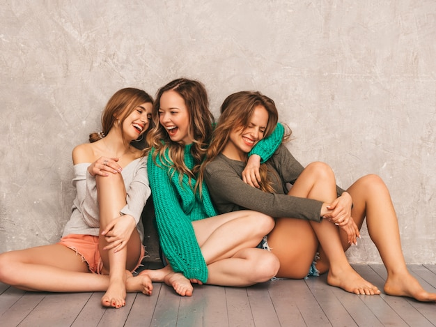 Tre giovani belle ragazze sorridenti splendide in abiti estivi alla moda. posa sexy spensierata delle donne. modelli positivi che si divertono. sedendo sul pavimento Foto Gratuite