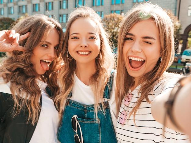 Tre giovani donne sorridenti dei pantaloni a vita bassa in vestiti di estate ragazze che prendono le foto dell'autoritratto del selfie sullo smartphone modelli che posano nella via femmina che mostra le emozioni positive del fronte Foto Gratuite