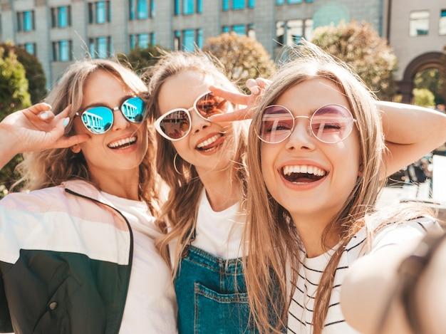 Tre giovani donne sorridenti dei pantaloni a vita bassa in vestiti di estate ragazze che prendono le foto dell'autoritratto del selfie sullo smartphone modelli che posano nella via femminile che mostra le emozioni positive del fronte in occhiali da sole Foto Gratuite