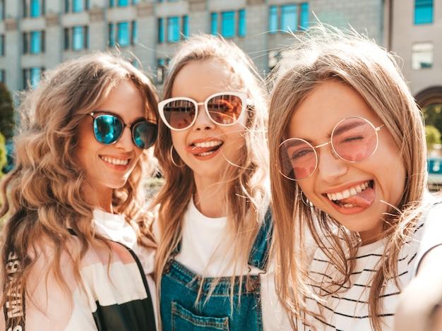 Tre giovani donne sorridenti dei pantaloni a vita bassa in vestiti di estate ragazze che prendono le foto dell'autoritratto del selfie sullo smartphone modelli che posano nella via femminile che mostra le emozioni positive del fronte mostrano la lingua Foto Gratuite