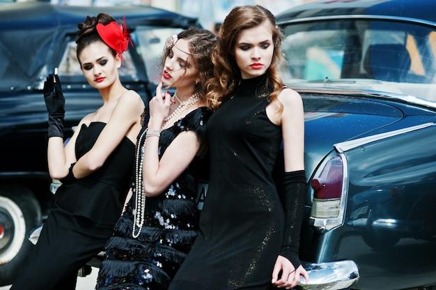 Tre giovani ragazze in abito in stile retrò vicino vecchie auto d'epoca classiche. Foto Premium