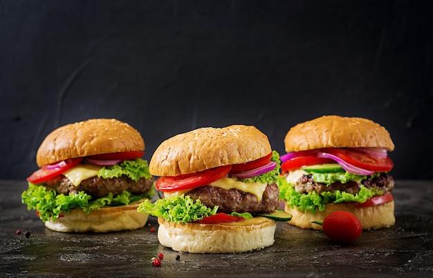 Tre hamburger con hamburger di carne di manzo e verdure fresche su sfondo scuro. Foto Premium