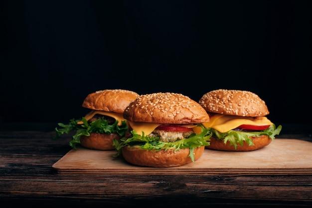 Tre hamburger fatti in casa con carne, formaggio, lattuga, pomodoro su un tavolo di legno Foto Premium