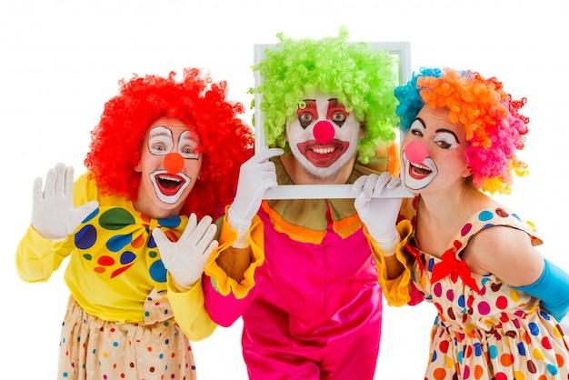 Tre pagliacci giocosi tenendo facce buffe. Foto Premium