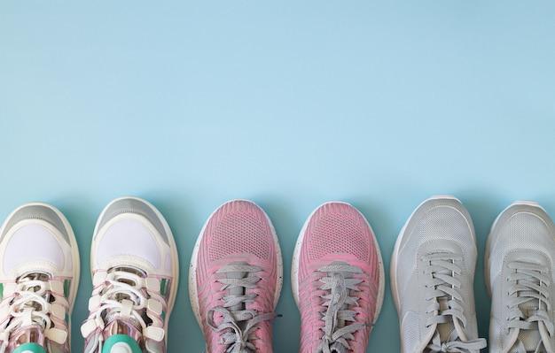 Tre paia di scarpe sportive vista dall'alto su sfondo azzurro con spazio di copia Foto Premium