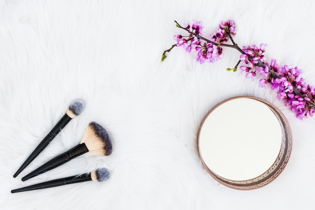 Tre pennelli trucco con specchio rotondo e ramoscello fiore artificiale su sfondo di pelliccia bianca Foto Gratuite