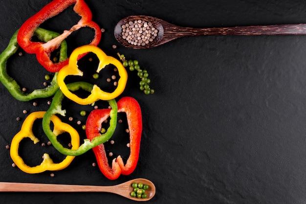 Tre peperoni dolci su un fondo di legno, cucinando insalata di verdure Foto Premium