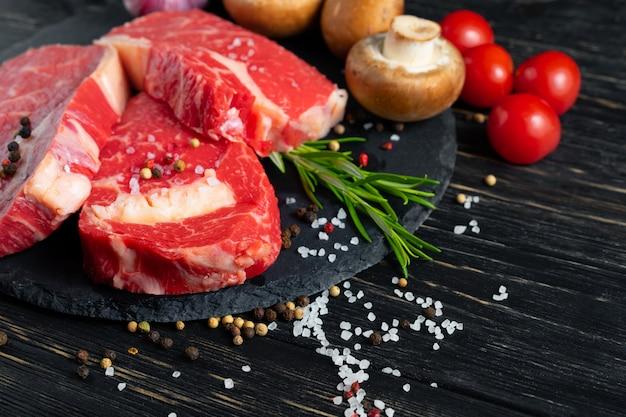 Tre pezzi di succosa carne cruda su un tagliere di pietra su un tavolo di legno nero Foto Premium