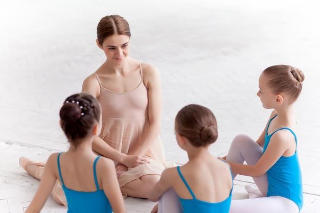 Tre piccole ballerine che ballano con l'insegnante di balletto personale nello studio di danza Foto Gratuite