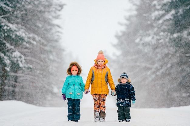 Tre piccoli bambini divertenti che si tengono per mano e che stanno sulla strada vicino al legno in tempo nevoso tempestoso di inverno. due ragazze con il ritratto all'aperto della natura del ragazzo su fondo astratto. attenzione: bambini su strada Foto Premium